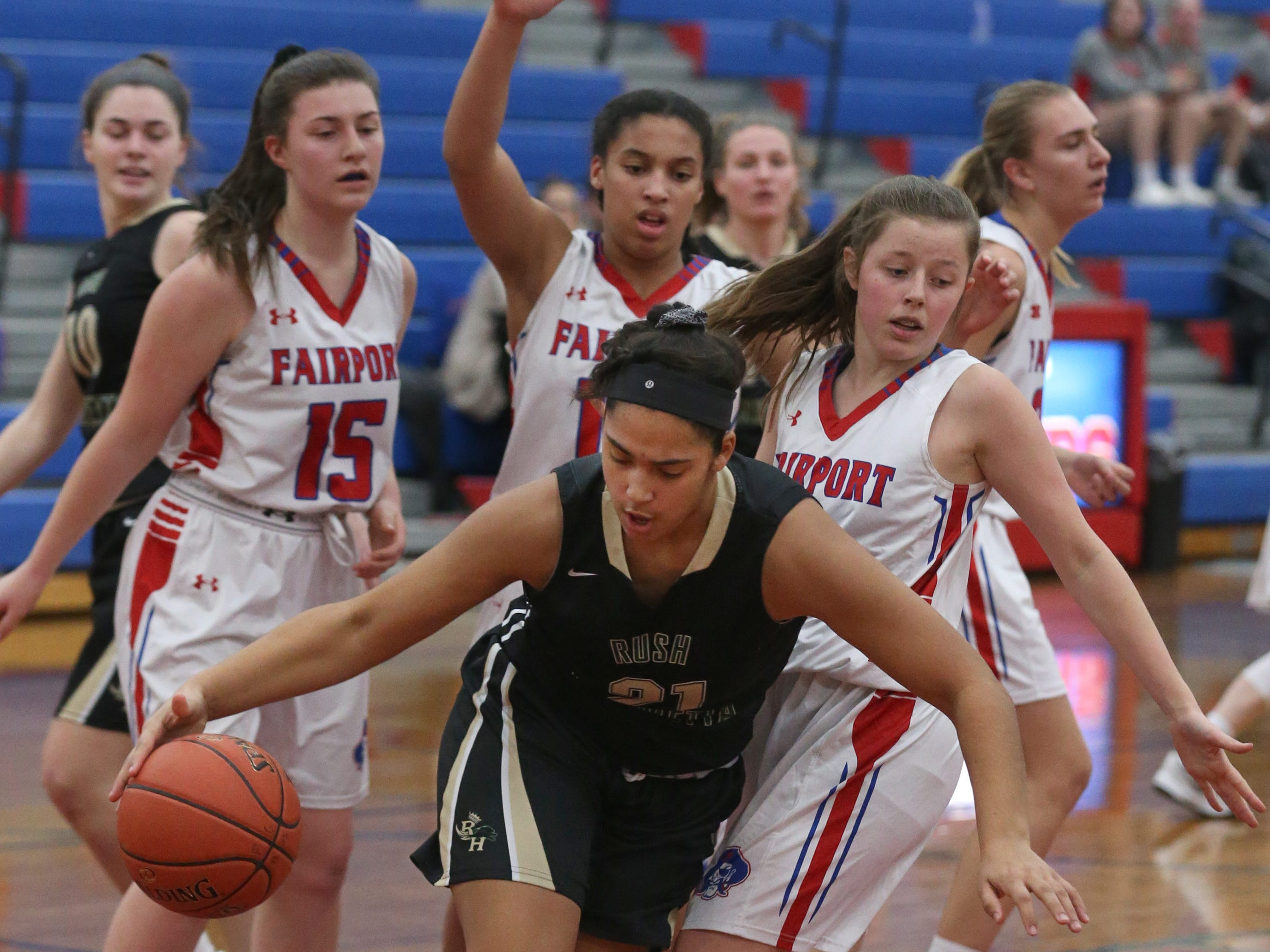 Rush-Henrietta's Gabby Garrett, center, looks for room to move as she pulls down a defensive rebound while surrounded by Fairport's Kat Zimmerman, left, Ella Meabon, center, and Abigail Smith, right.