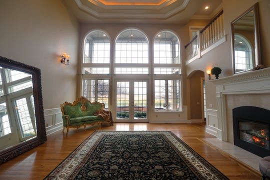 A large living room with a grand entryway and high ceiling greet visitors to this Victor mansion on the market for $975,000.