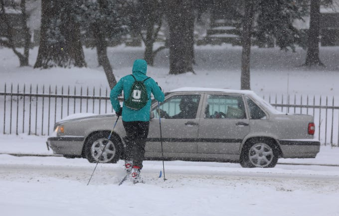 A skier crosses Mt. Hope Ave. to head to Mt. Hope Cemetery to cross country ski Tuesday, Feb. 12, 2019.
