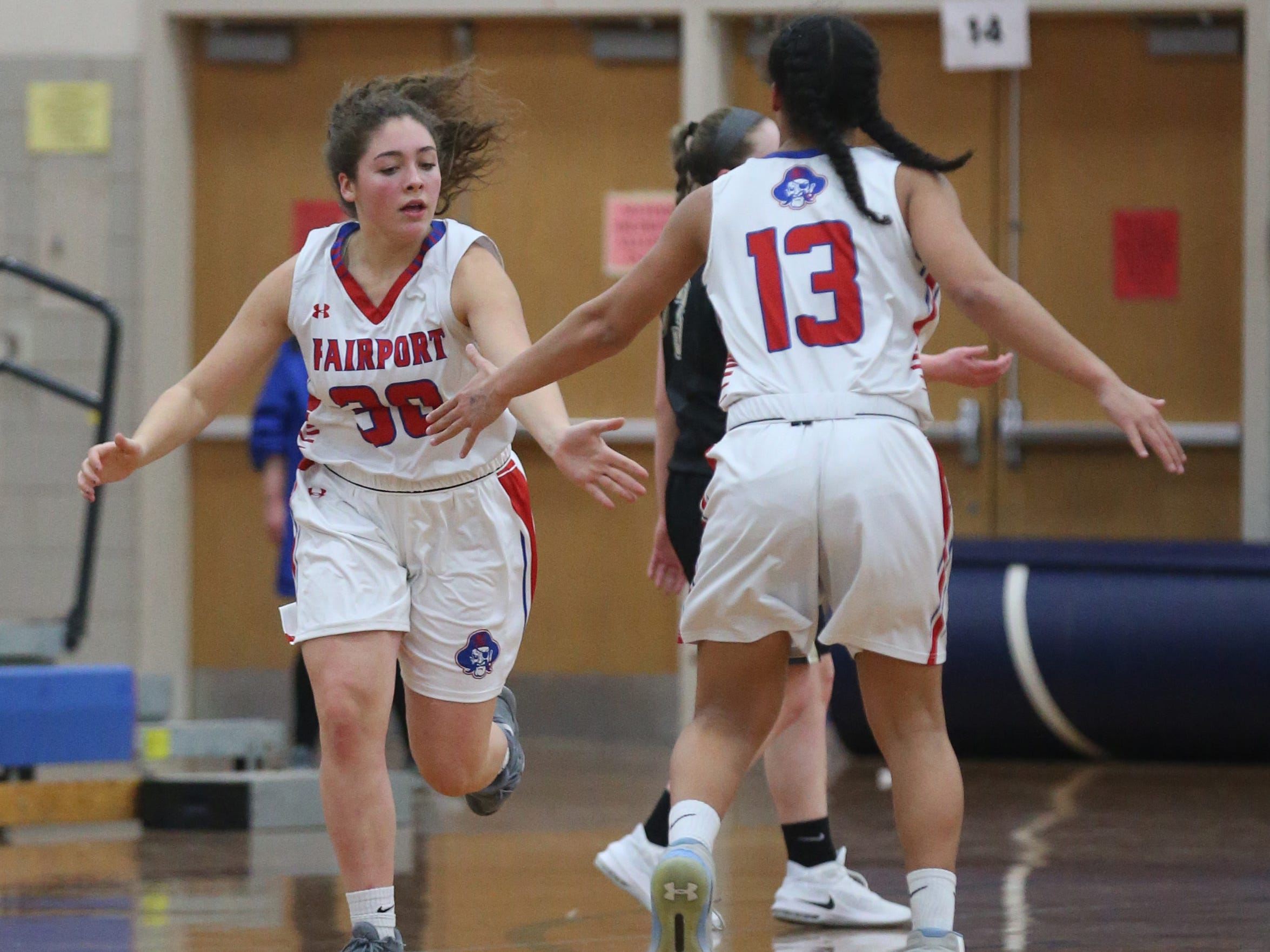 Fairport's Bryn Holmes, left, celebrates her basket with teammate Ella Meabon, right, as they head back down court.