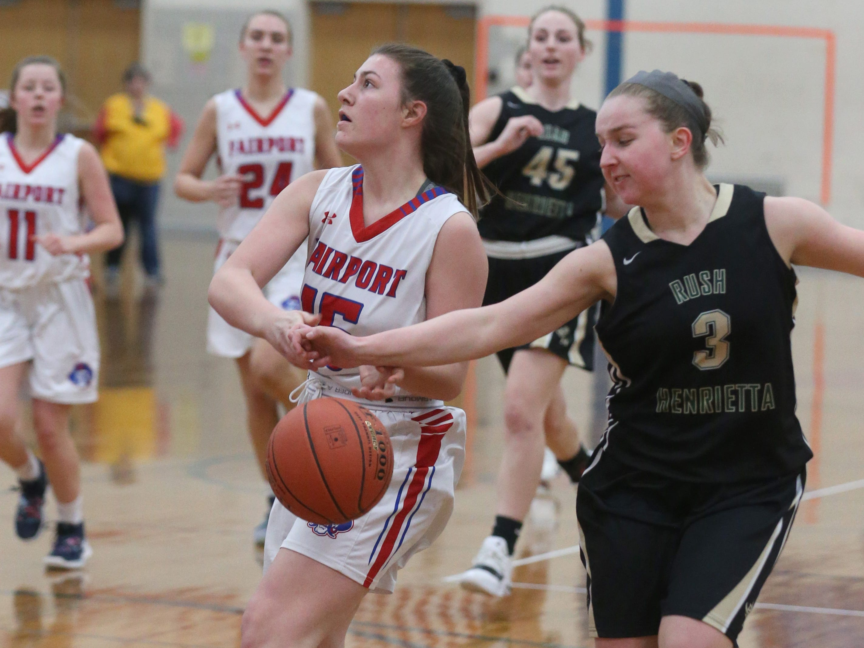 Rush-Henrietta's Logan Taylor, right, races back on defense to strip the ball away from Fairport's Kat Zimmerman before she can complete her layup.