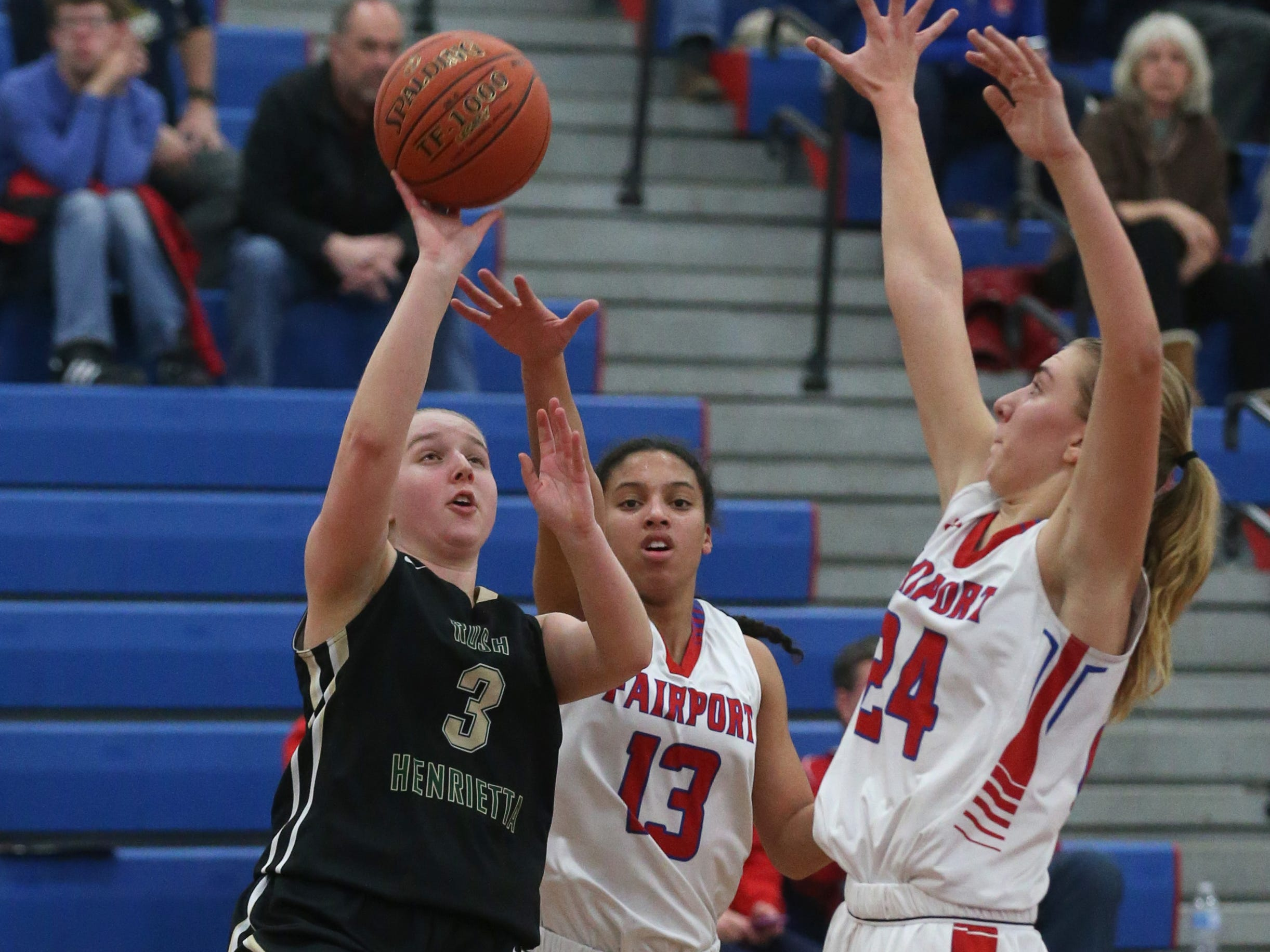 Rush-Henrietta's Logan Taylor, left, puts up a running shot as Fairport's Ella Meabon, center, and Riley DeRue, right, defend.