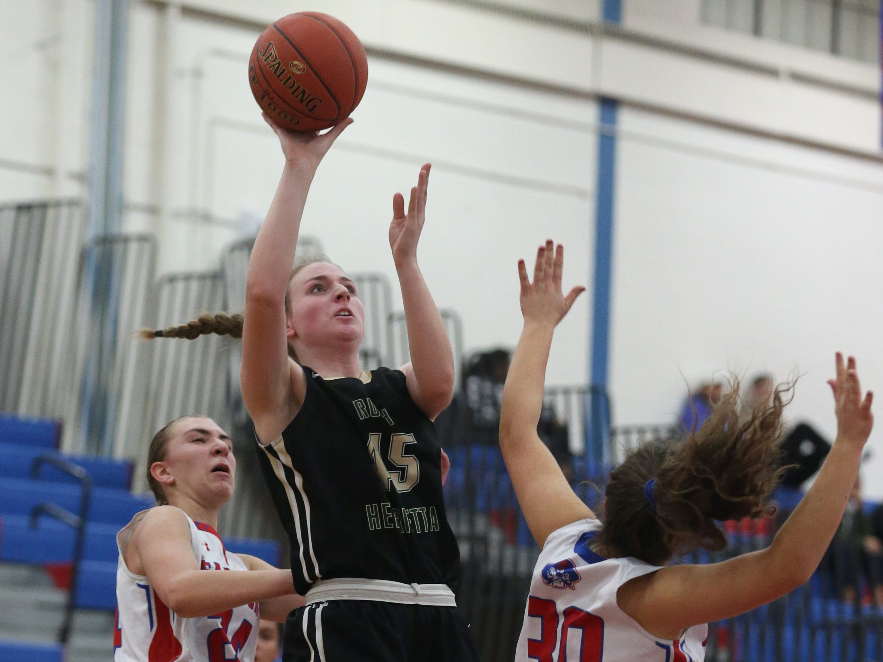 Rush-Henrietta's  Rebecca Gregg, center, puts up a shot between Fairport's Bryn Homes, right, and Riley DeRue, left.