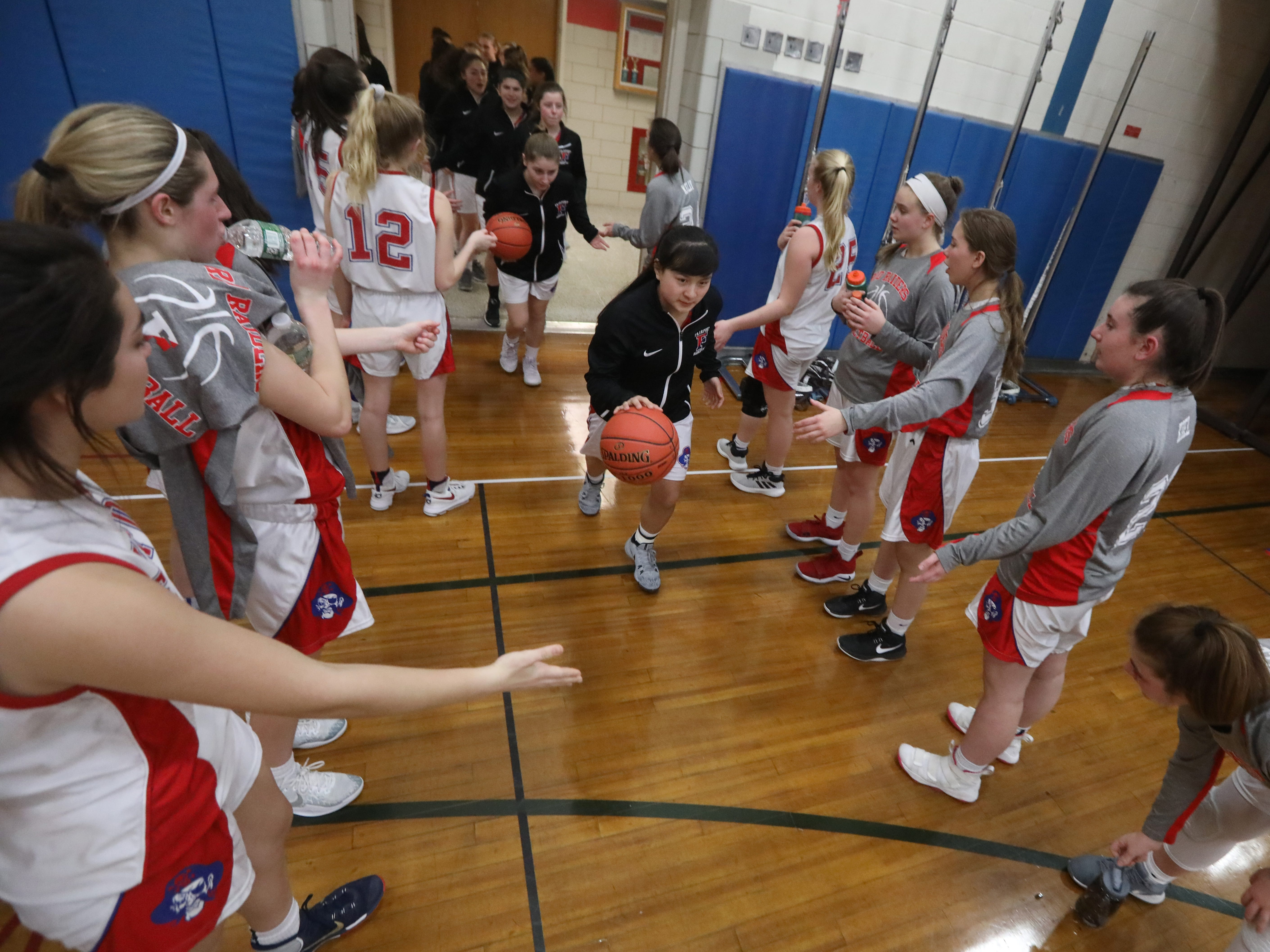 Fairport guard Kate Miller leads the varsity girls out of the locker room and past the cheering JV squad as they take the floor before their game against Rush-Henrietta.