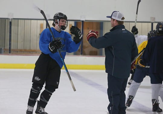Blake Humphrey, a junior at Penfield High, left, gets a high-five from instructor Chris Collins as he works through individual skating drills at Collins' Evolve Hockey at the the Village Sports rink in Perinton  on Tuesday, Feb. 12, 2019.