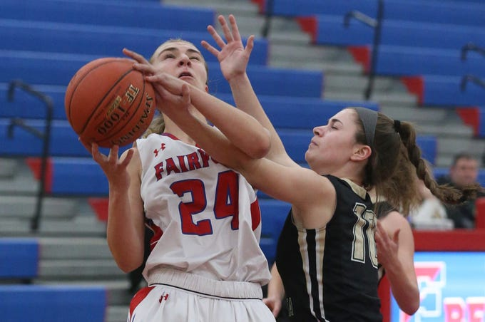 Fairport's Riley DeRue, left, is tied up by the defense of Rush-Henrietta's Rachel Crane, right, as she tries to score from close in during their game at Fairport High School Monday, Feb. 11.