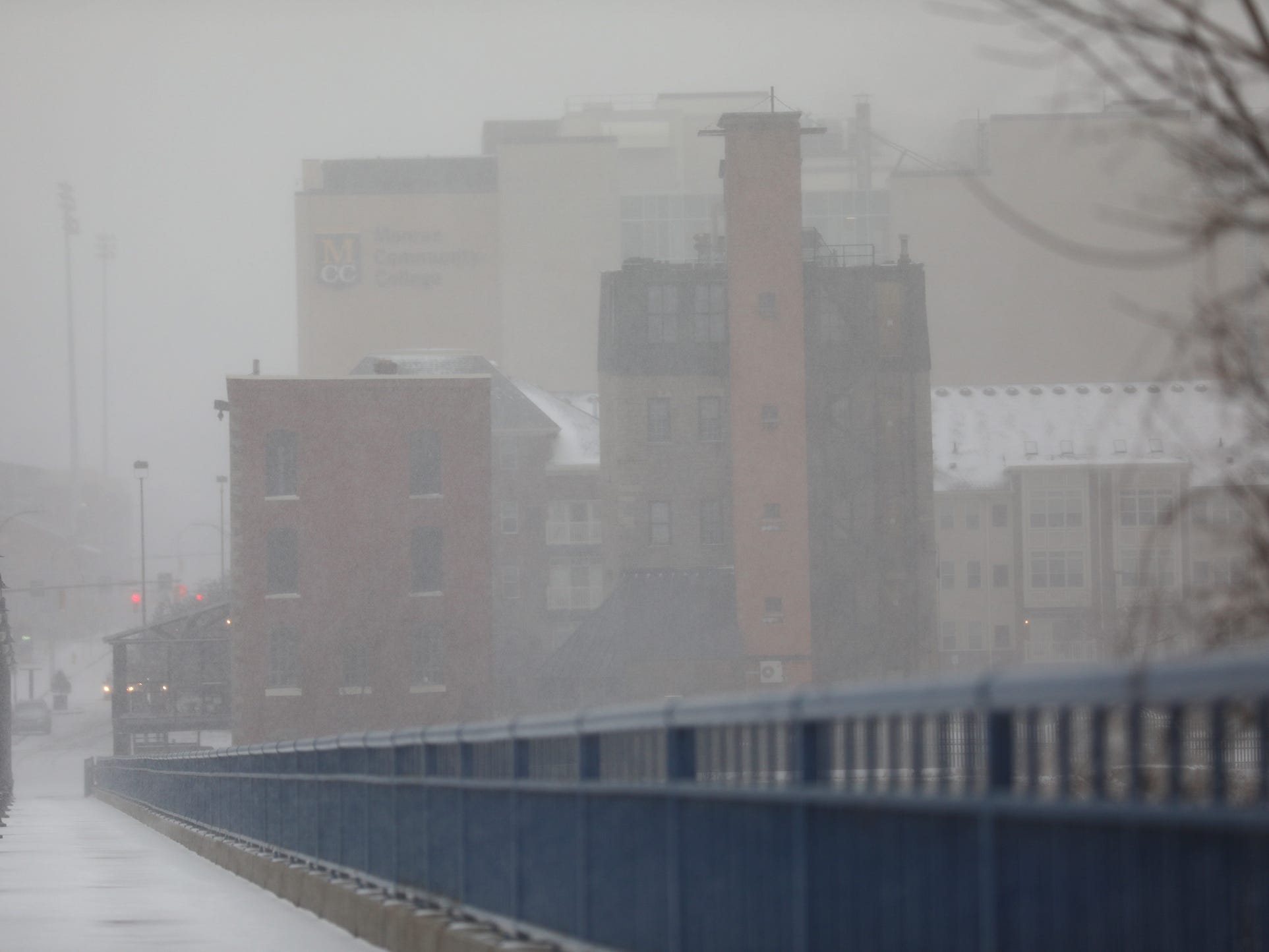 Snow coming down almost hides High Falls from the Pont de Rennes Bridge.