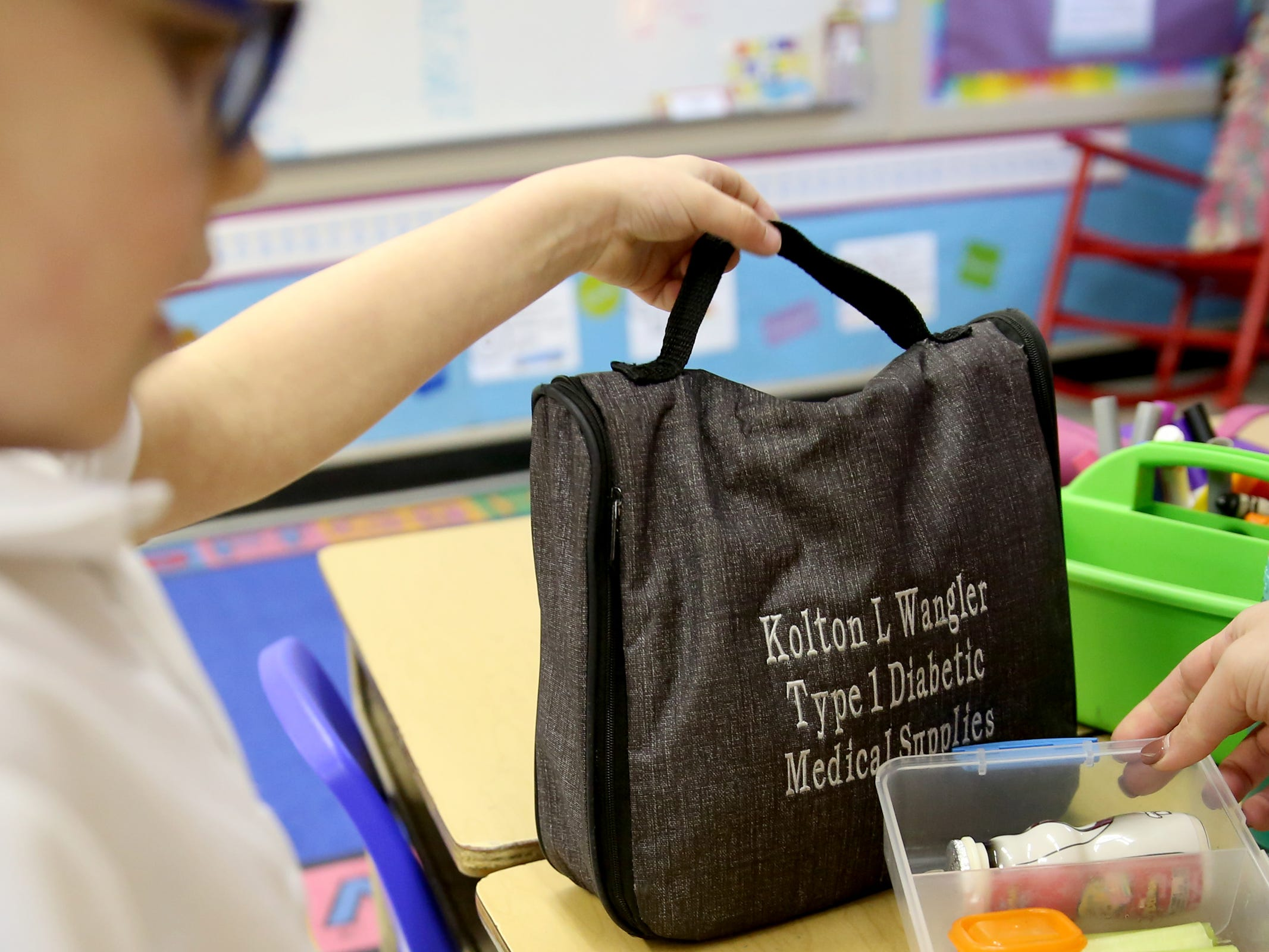 Jessica Wangler and her son, Kolton Wangler, 6, who has Type 1 diabetes, grab his bag of medical supplies as she monitors his insulin dosage during his lunch break in his kindergarten classroom at St. Joseph Catholic School in Salem on Tuesday, Feb. 12, 2019. Wangler works in Sen. Peter Courtney's office, and when he heard her story he introduced a bill to allow people to get emergency insulin from the pharmacy.