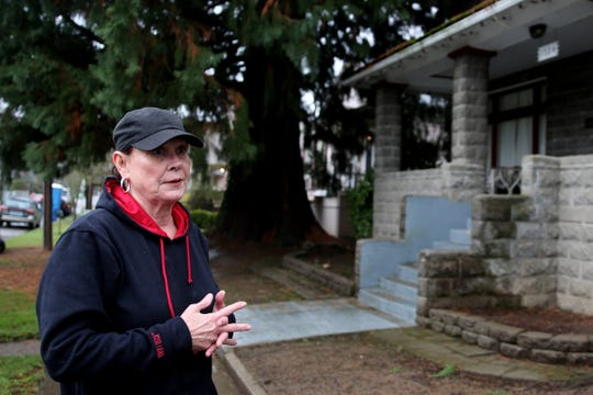 Neighbor Janet Strauch speaks about the effect two giant sequoia trees have had on her property in front of a historic home on Chemeketa St. NE. The city of Salem has denied an appeal for removal of the trees after the property owner didn't provided documentation that their roots were causing damage to home's basement, sidewalk and a neighbor's driveway. Photographed in Salem on Tuesday, Feb. 12, 2019.