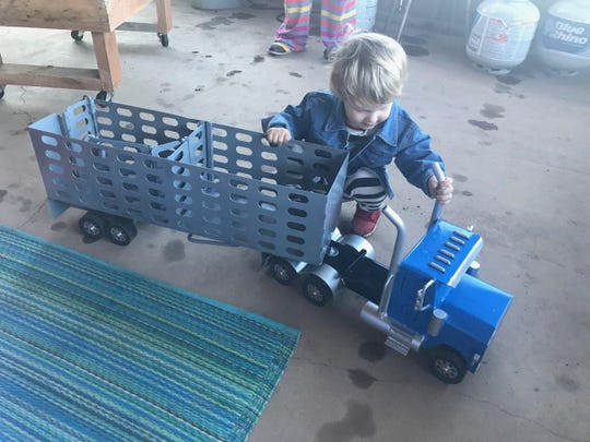 A child tests out the cattle trailer and semi truck toy from The Happy Toy Maker. All of the products are made in Happy, Texas.