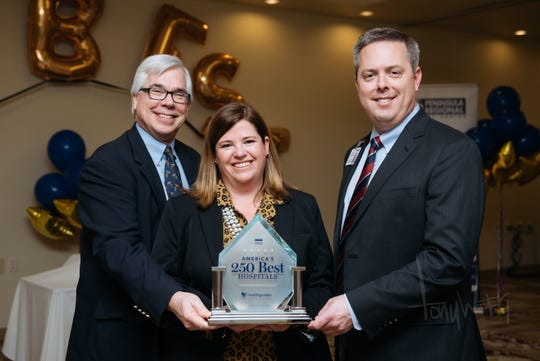 Accepting PRMC's America's 250 Best Hospital award from Healthgrades Director of Quality Solutions Maggie Foley, center, are C.B. Silvia, MD, vice president of medical affairs and chief medical officer at PRMC, left, and Steve Leonard PRMC's President/CEO.