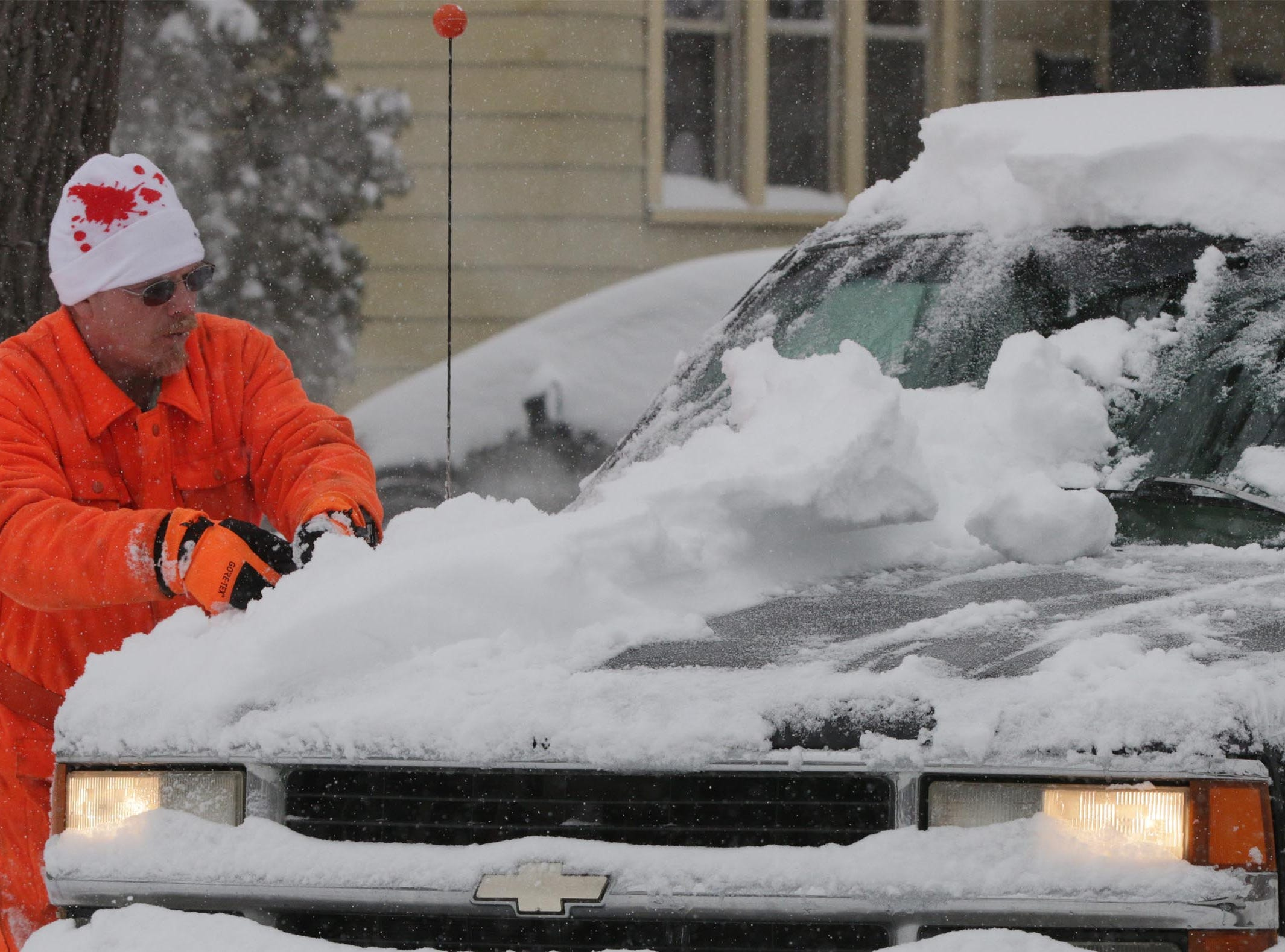 Clifton Hart clears off his truck on North 8th Street following snowfall, Tuesday, February 12, 2019, in Sheboygan, Wis.