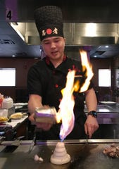The chef lights an onion volcano at the Umi Sushi And Steak House, Thursday, January 31, 2019, in Sheboygan, Wis.
