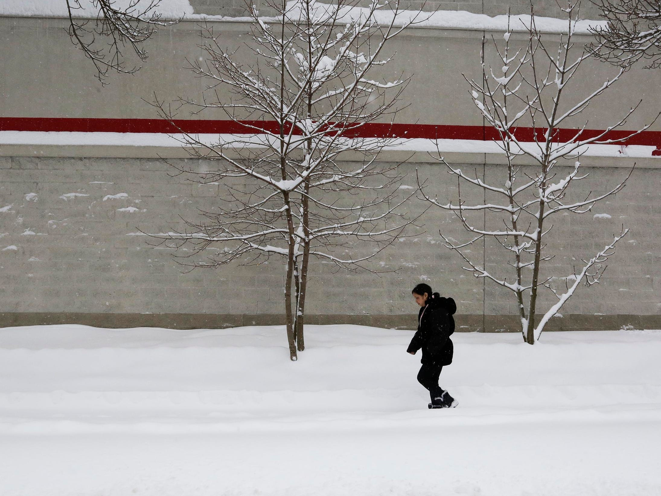 Pao Yang walks on a North 8th Street sidewalk on a fresh blanket of snow, Tuesday, February 12, 2019, in Sheboygan, Wis.