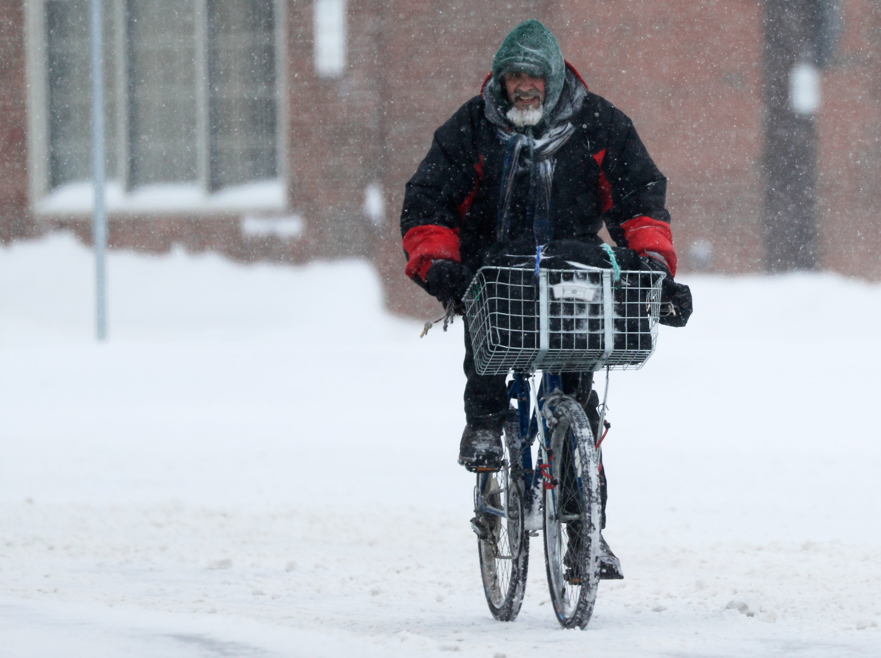 A cyclist rides along University Ave during a snowstorm on Tuesday, February 12, 2019 in Green Bay, Wis.