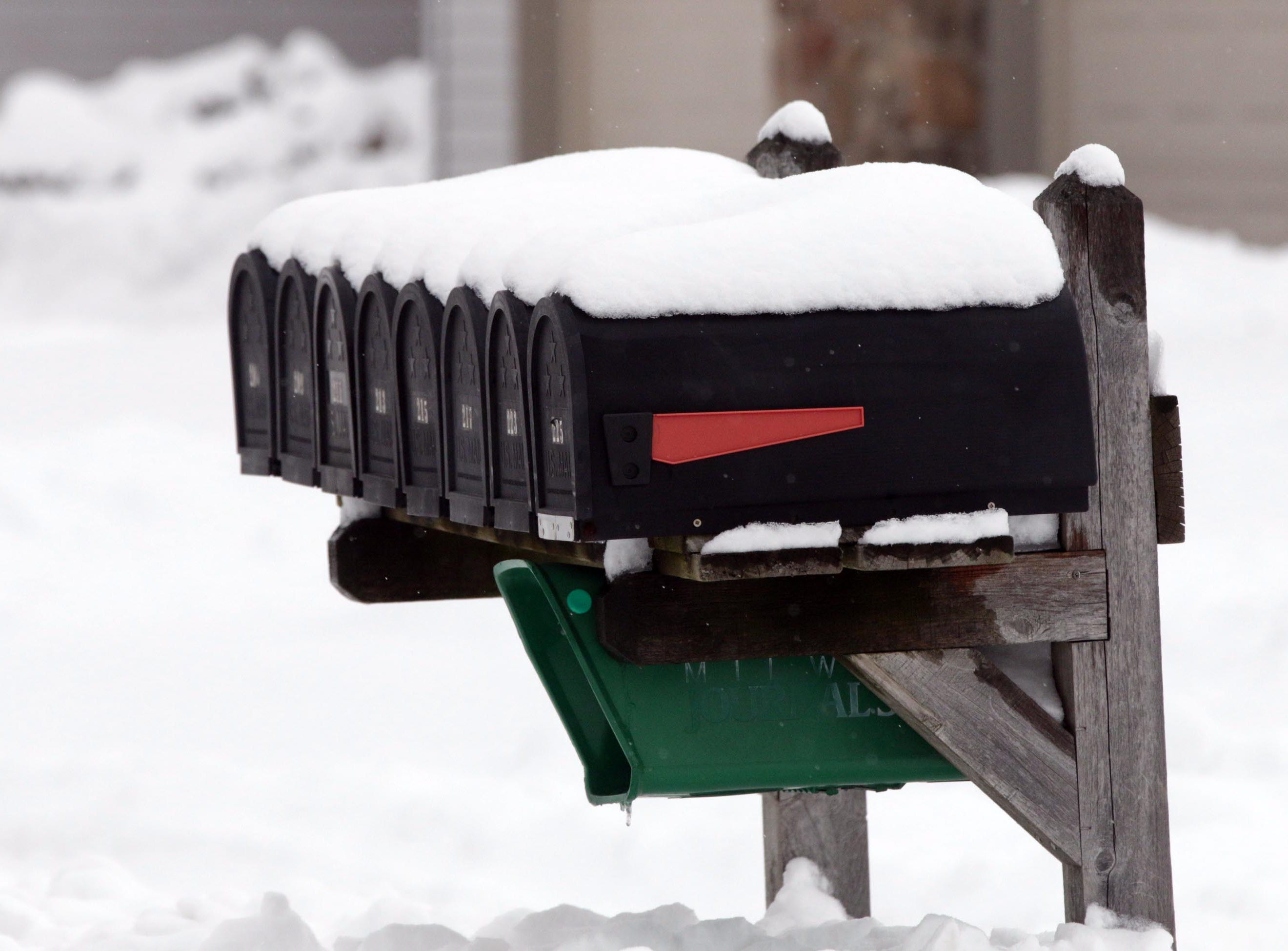 Snow covers a line of mail boxes, Tuesday, February 12, 2019, in Plymouth, Wis.