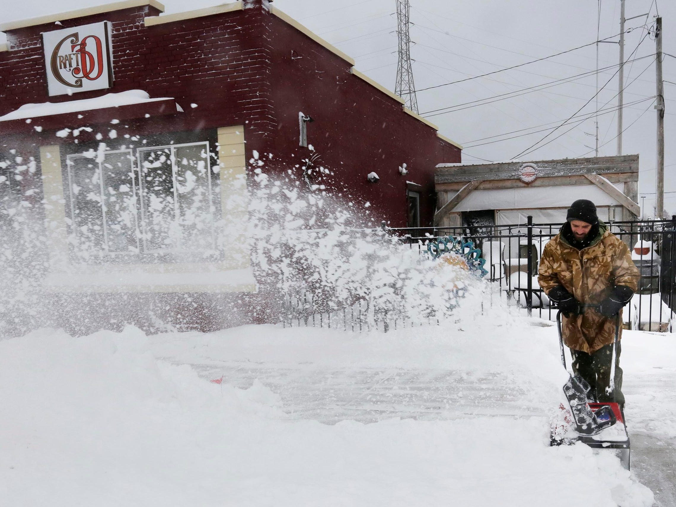Dan Shaw blows snow near Craft 30 on South 10th Street, Tuesday, February 12, 2019, in Sheboygan, Wis.