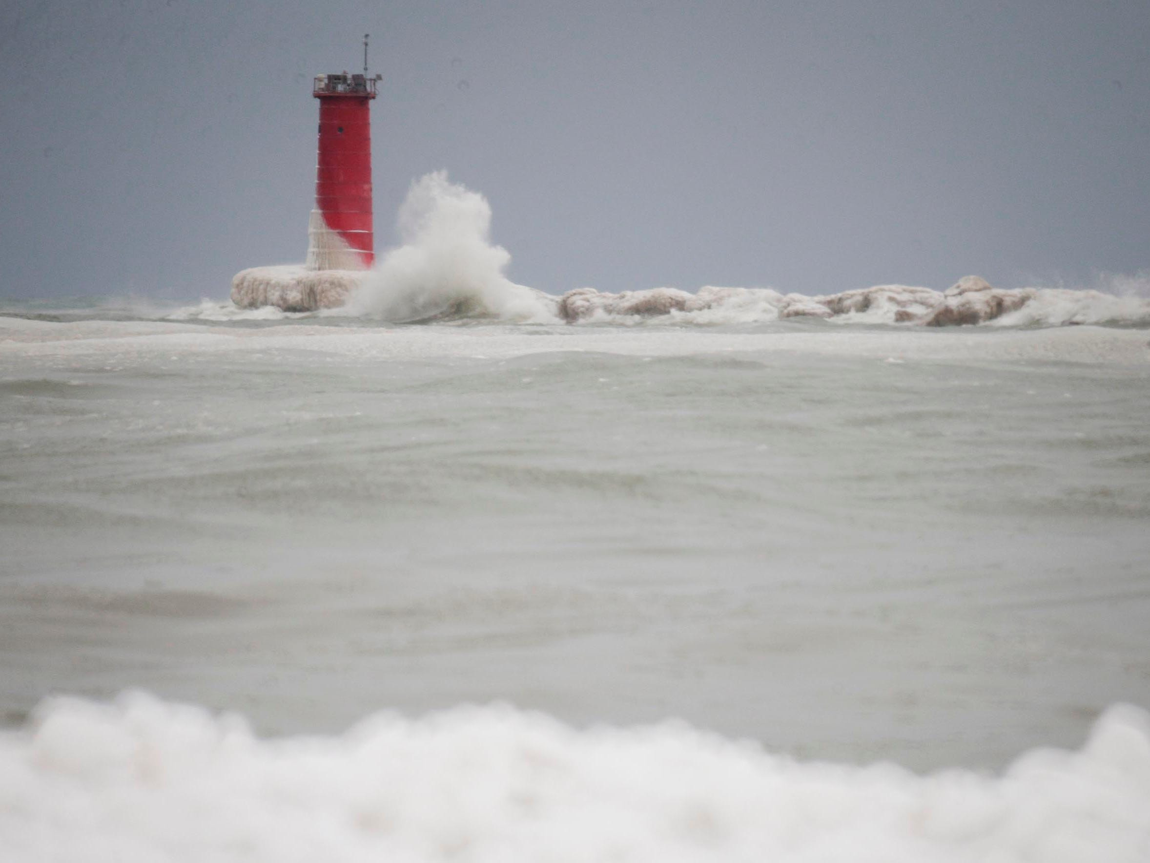 Waves crash on the Sheboygan lighthouse, Tuesday, February 12, 2019, in Sheboygan, Wis. A winter storm dumped snow on the city and stirred up Lake Michigan.