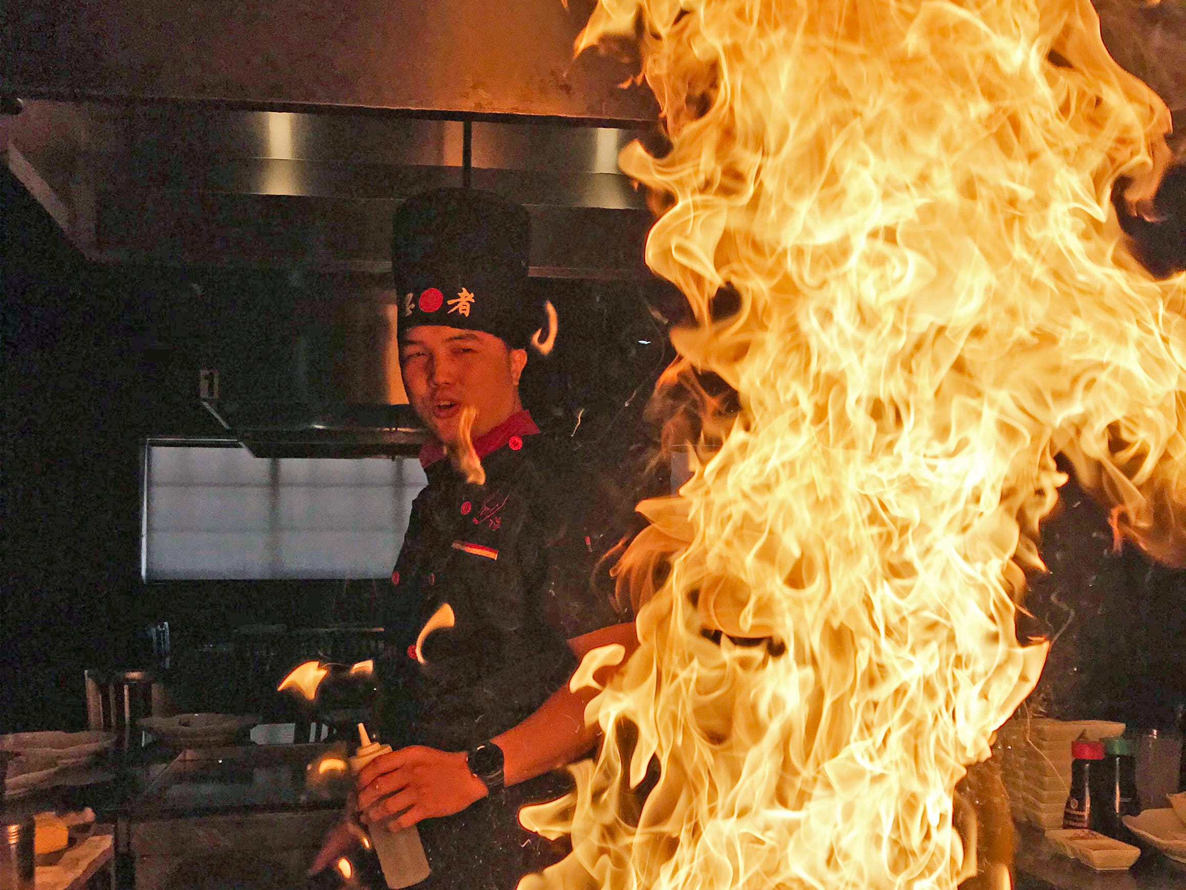 The chef is dwarfed by the flames at the Umi Sushi And Steak House, Thursday, January 31, 2019, in Sheboygan, Wis.