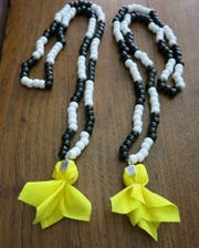 """New Orleans Saints-inspired, hand-made Mardi Gras """"penalty bead' throws are available at Krewe Centaur Den Bead Room."""