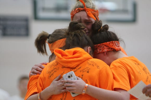 Ava Tunheim's friends, also members of her eighth grade basketball team, share a hug after reading a letter from Ava's dad before the start of the varsity boys game Monday night.