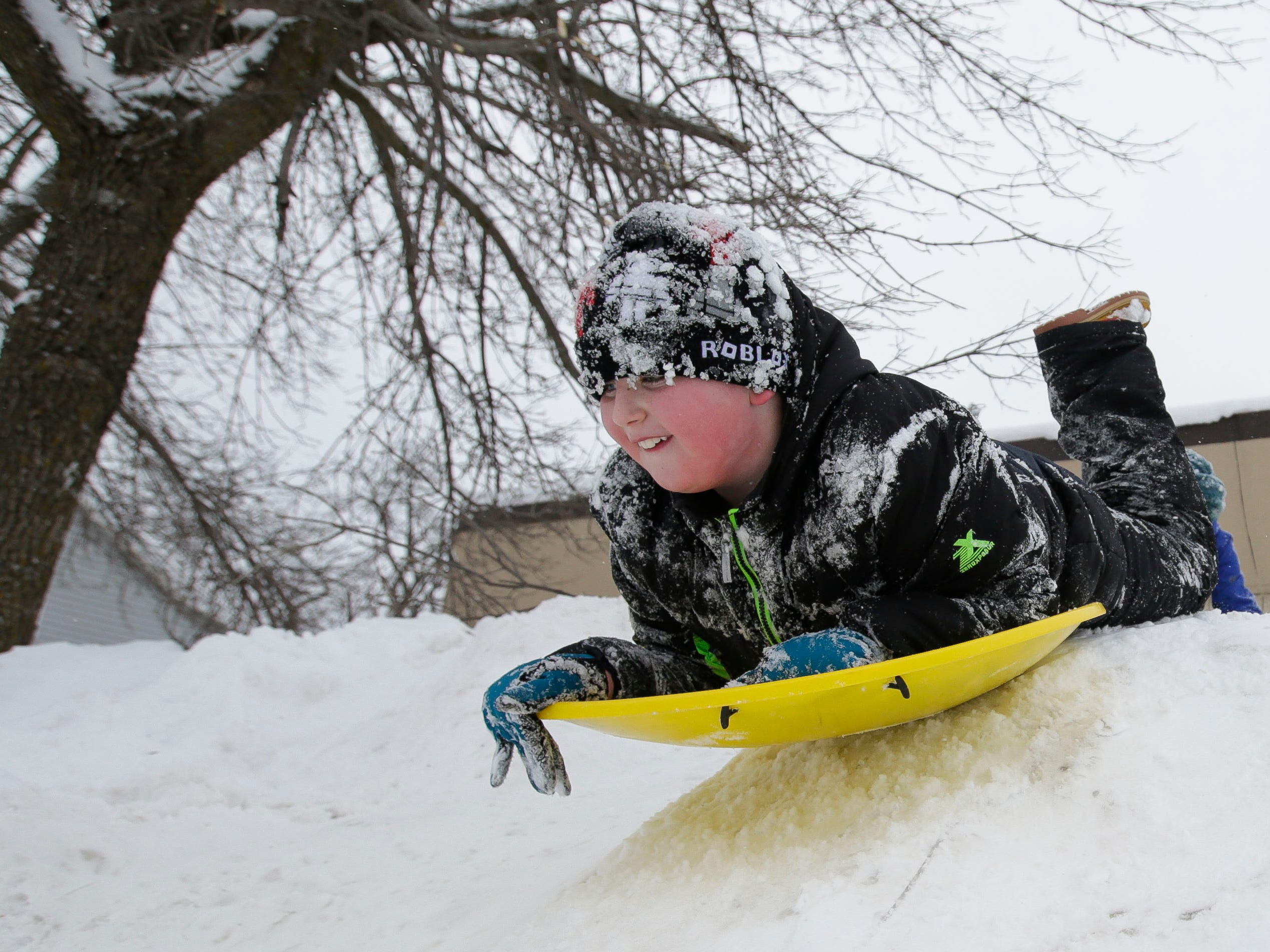 Holden Fritsche, 8, sleds on a pile of snow on Tuesday, February 12, 2019, in Stevens Point, Wis. A winter storm is expected to drop 8-11 inches of snow in central Wisconsin before clearing Tuesday night.