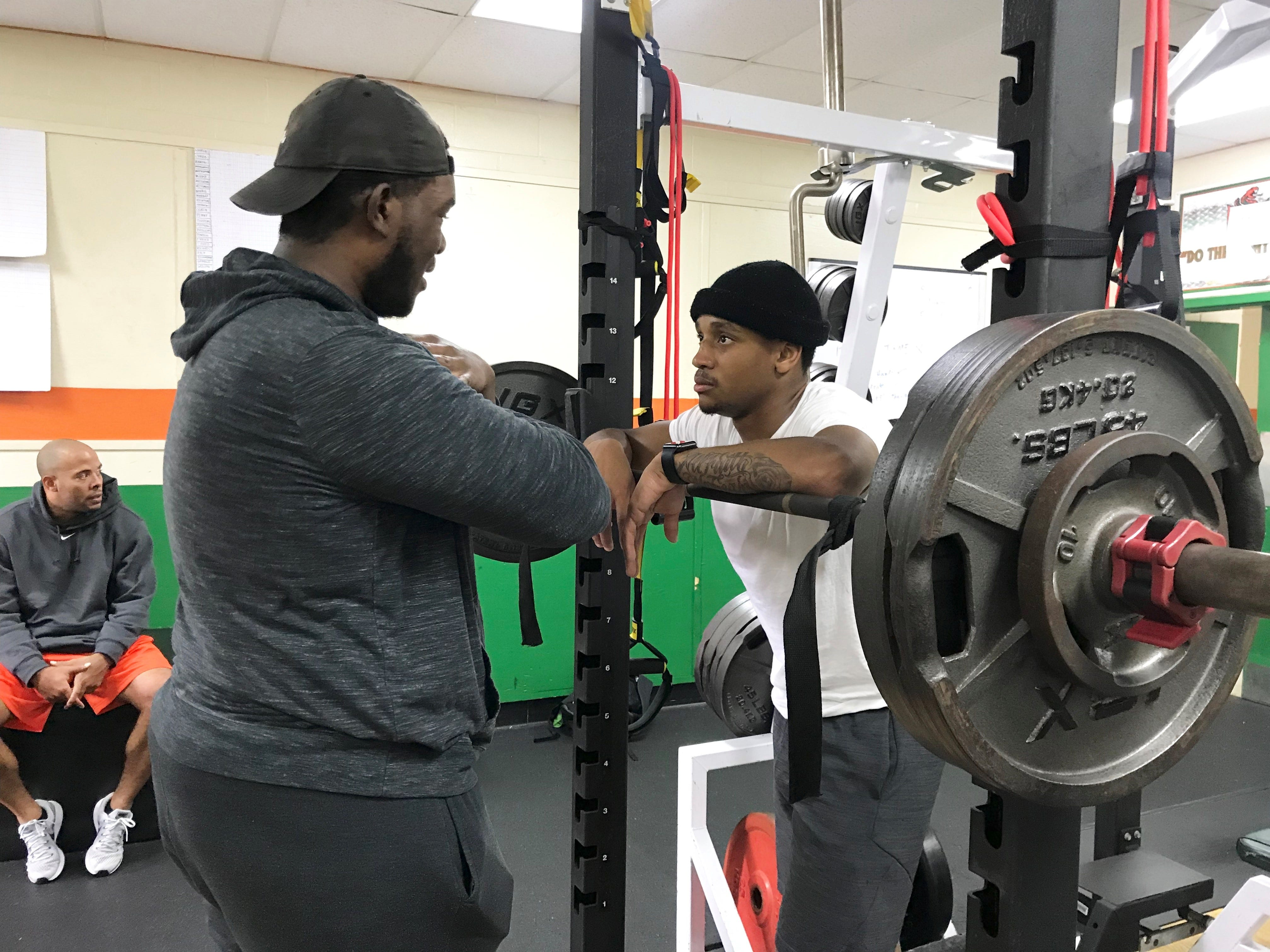 FAMU defensive back Herman Jackson listens attentively to assistant strength and conditioning coach Marcus Johnson  prior to starting his 245-pound front squat.