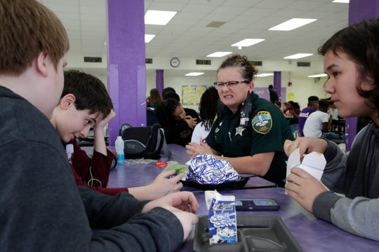 Leon County Sheriff's Department Deputy Jennifer Morris, school resource officer at Cobb Middle School, sits down with a group of students during lunch Tuesday, Feb. 12, 2019.