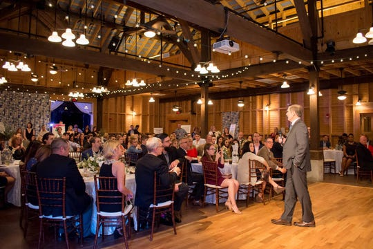 """Dale Tadlock, right, president and owner of Tadlock Roofing speaks at the Children's Home Society's """"Wish Upon a Star"""" fundraiser event."""