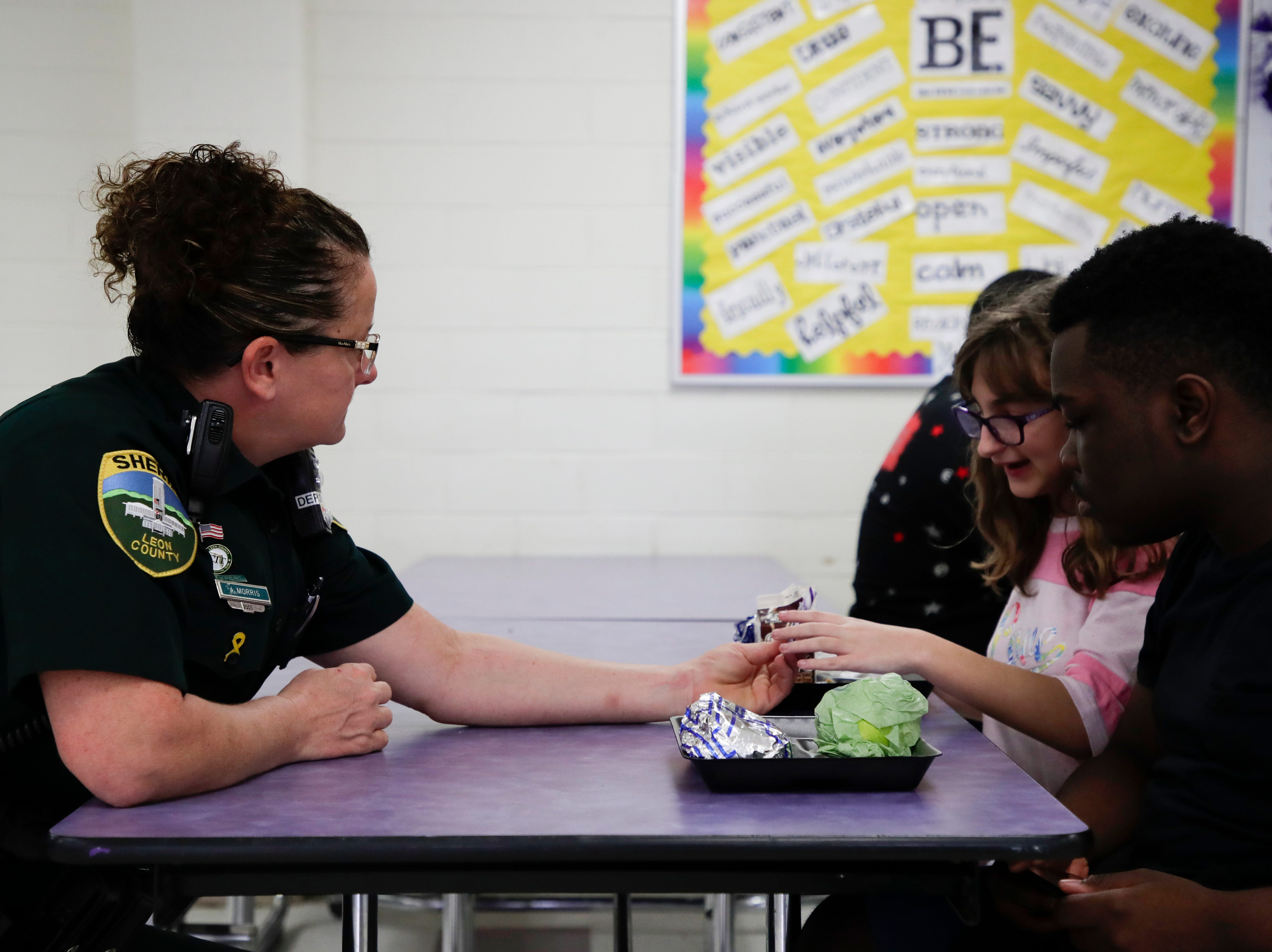 Leon County Sheriff's Department Deputy Jennifer Morris, school resource officer at Cobb Middle School, sits down with seventh grader Lenoris Nixson and his girlfriend and gives them each a piece of candy during lunch Tuesday, Feb. 12, 2019.