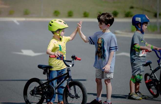 Grayson Irwin in yellow and Corbett Howell to his left give high fives at the 2018 Champions Ride.