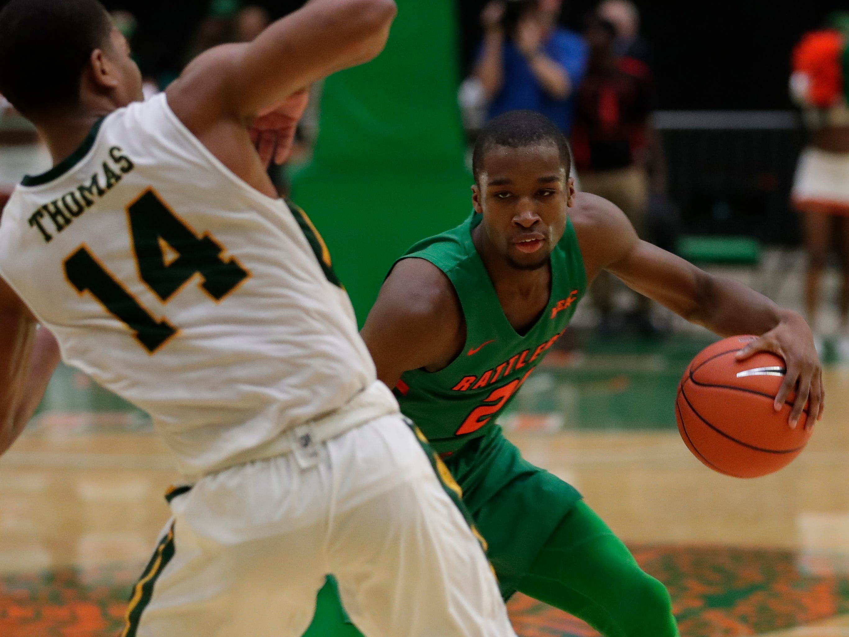 Florida A&M guard Justin Ravenel (21) dribbles around Nic Thomas of Norfolk State at the Alfred Lawson Jr. Multipurpose Center Monday, Feb. 11, 2019.
