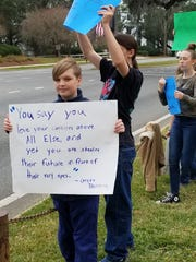 "Owen Bishop holds a sign with a quote from Greta Thunberg at the first School Strike for Climate in Tallahassee in January that says, ""You say you love your children above all else, and yet you are stealing their future in front of their very eyes."""