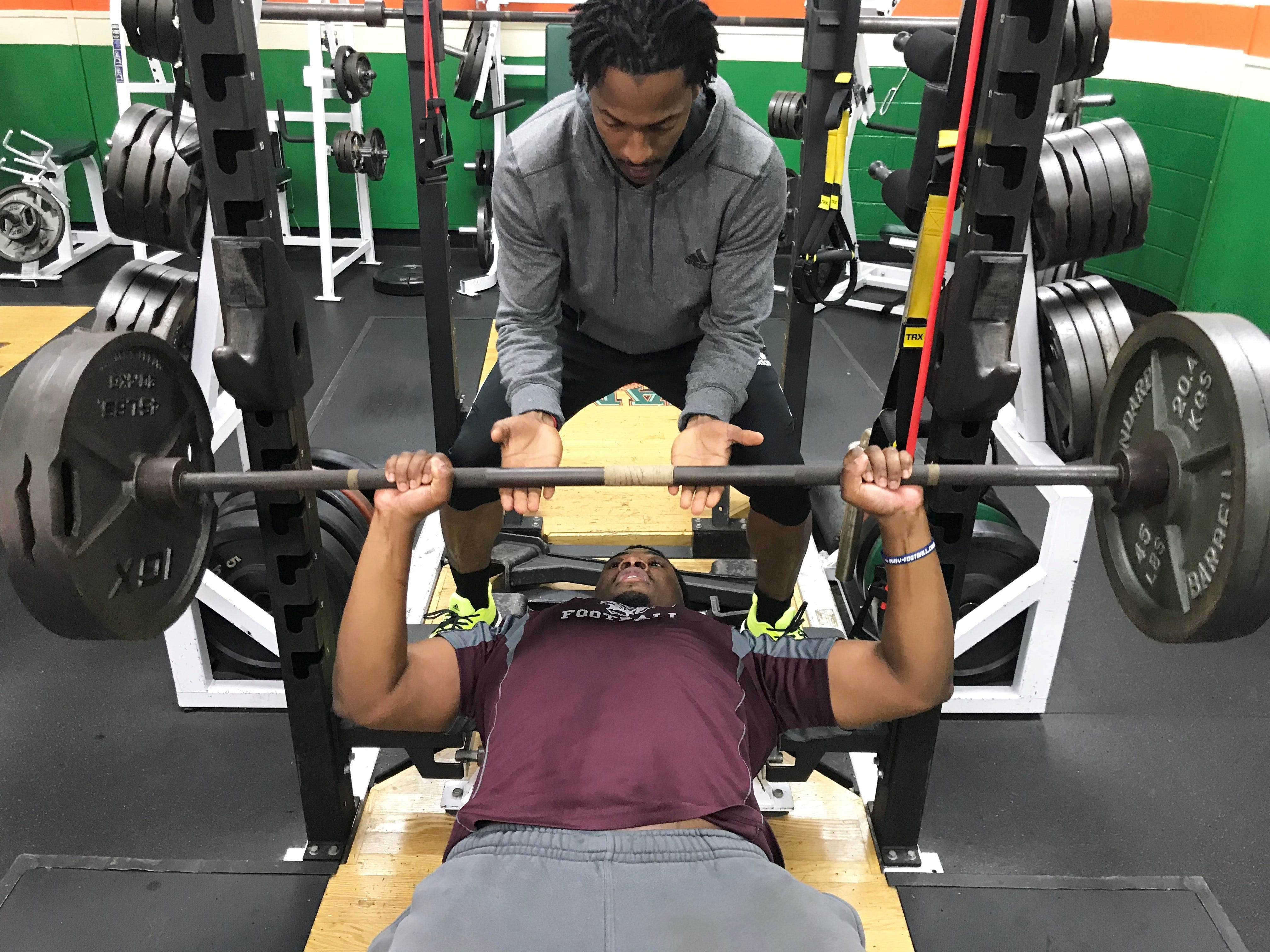 FAMU assistant strength and conditioning coach Mike Winters spots Tariq  Akbar with a bench press of 225 pounds.