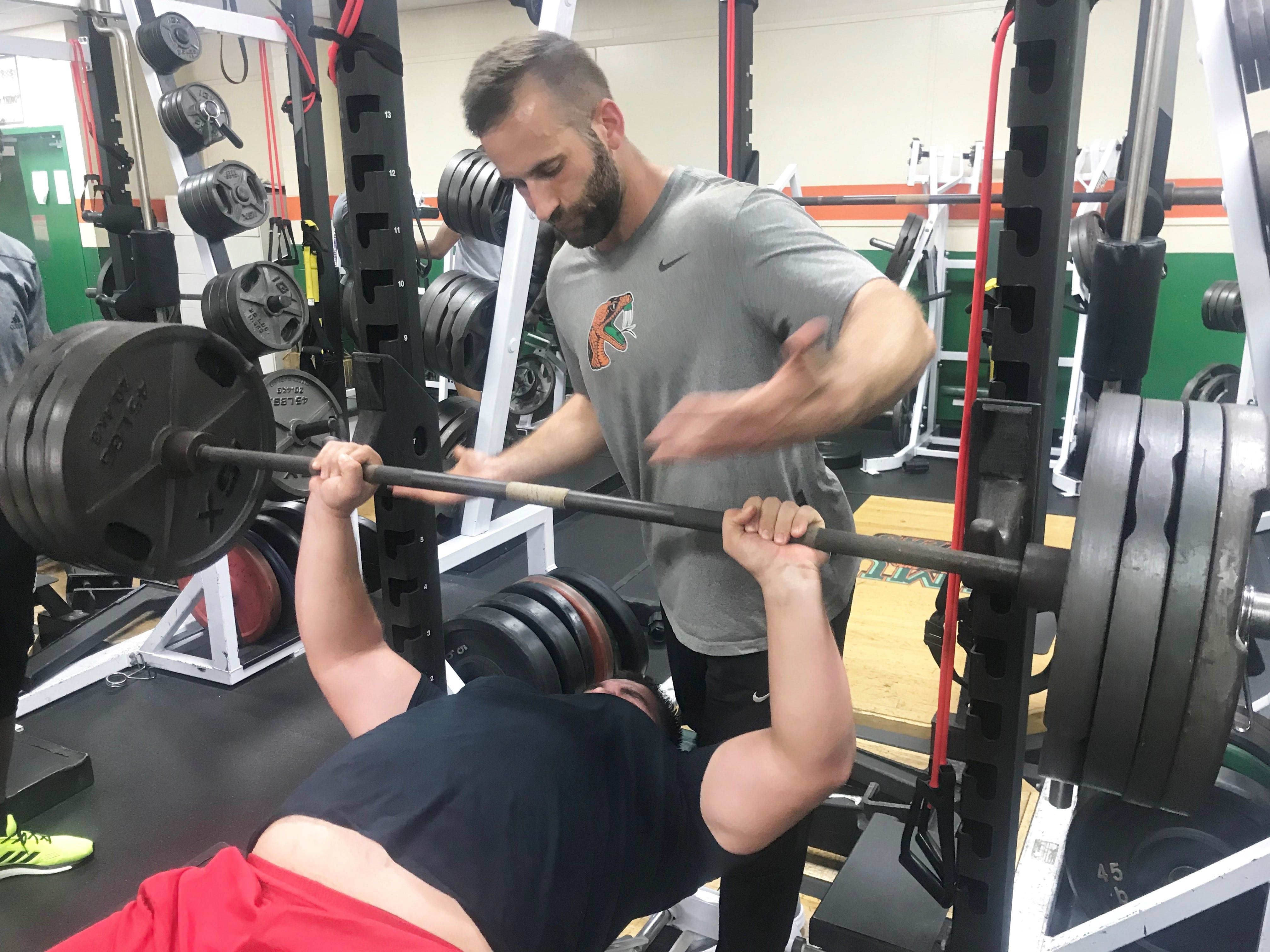 Offensive lineman Bradley Weatherington performs eight reps of bench presses at 400 pounds with FAMU strength and conditioning coach Parker Brooks.