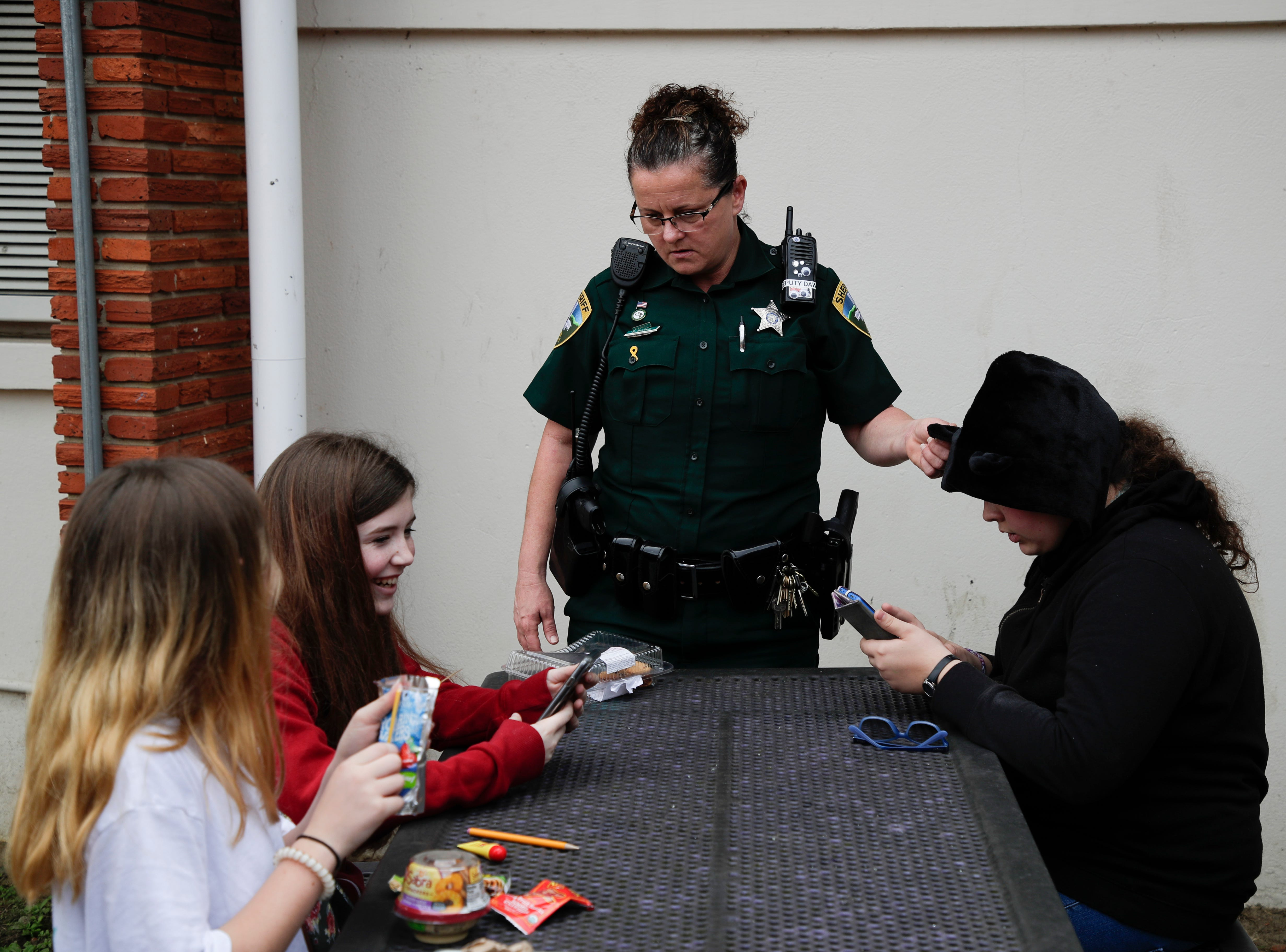 Leon County Sheriff's Department Deputy Jennifer Morris, school resource officer at Cobb Middle School, talks with a group of students during lunch Tuesday, Feb. 12, 2019.