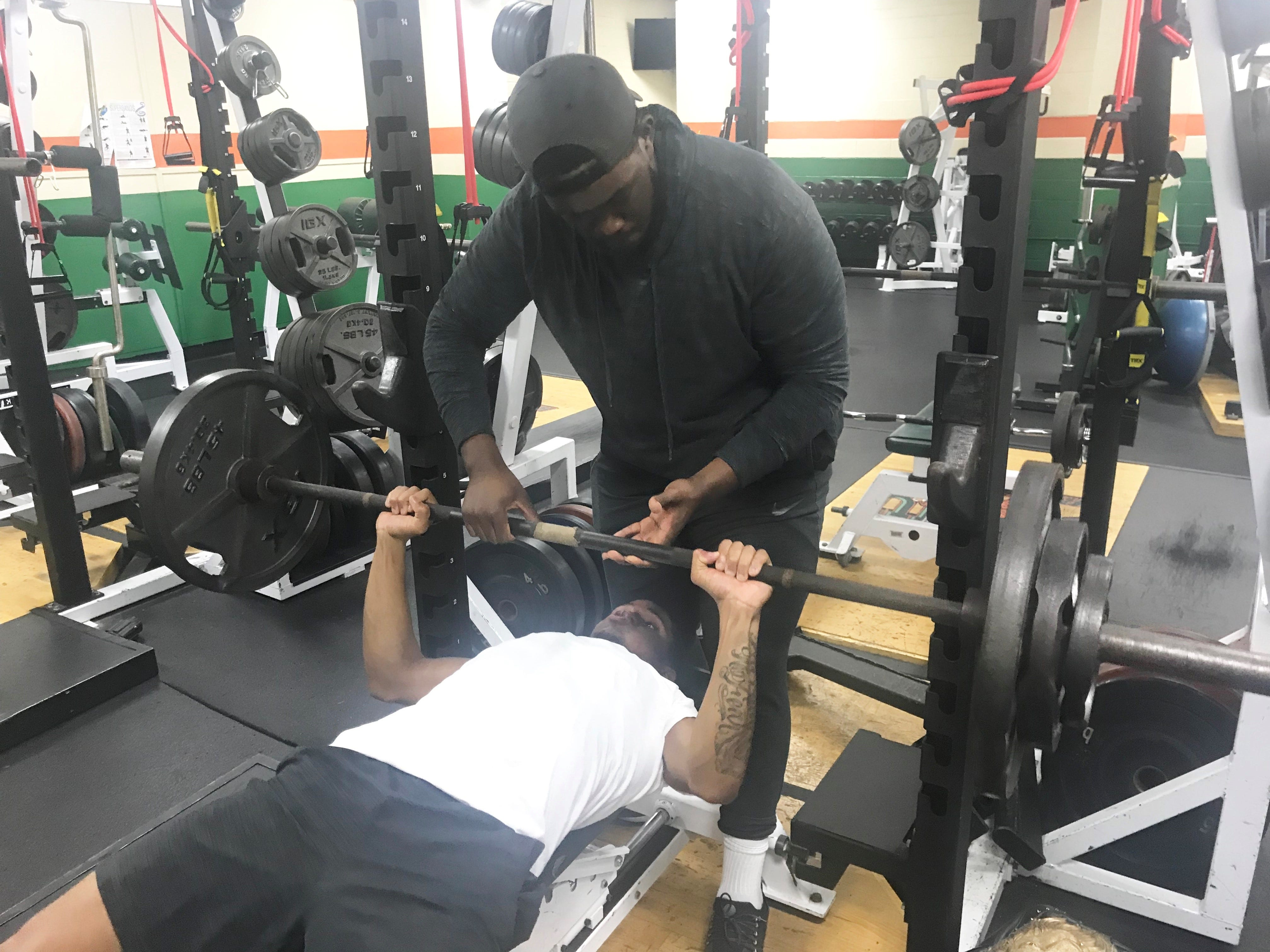 FAMU assistant strength and conditioning coach Marcus Johnson spots defensive back Herman Jackson on a bench press.