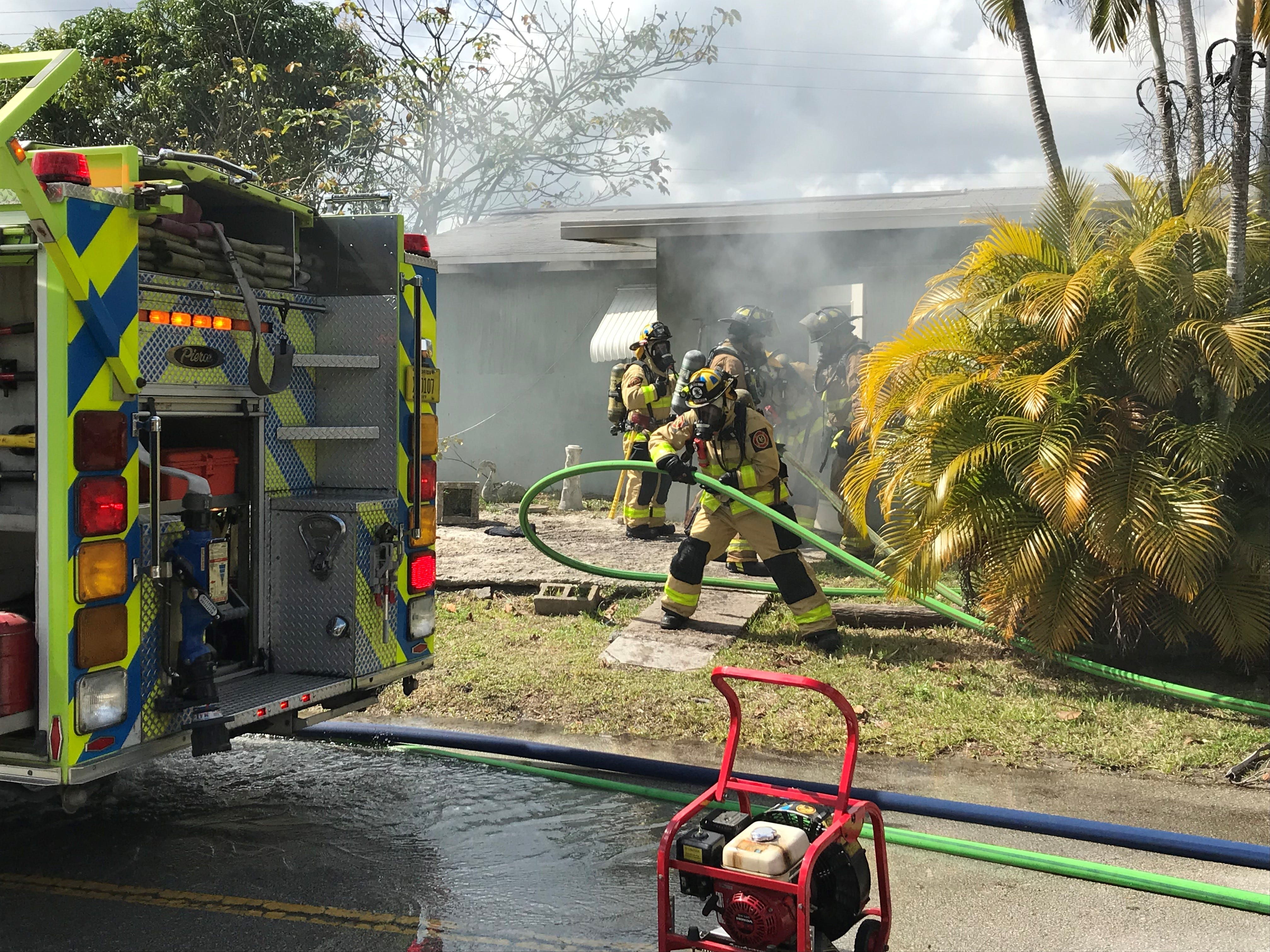 Firefighters work to extinguish a fire in the house along South East Central Avenue in Stuart.