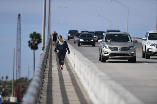 """Melanie Maldonado, of Port St. Lucie, comes down the southeast side of the South Bridge over the Indian River Lagoon during her daily walk for exercise on Sunday, Feb. 10, 2019, In Fort Pierce. """"I like to get a nice workout, beautiful weather, beautiful views,"""" Maldonado said, walking with her friend Thomas Moran, of Fort Pierce (background). """"The walkway is kind of narrow, it's hard if people are walking on the opposite side of you, you really got to move out of the way, It's on the narrow side."""" The county is asking FDOT to change the design of the bridge to make it safer for cyclists and pedestrians."""