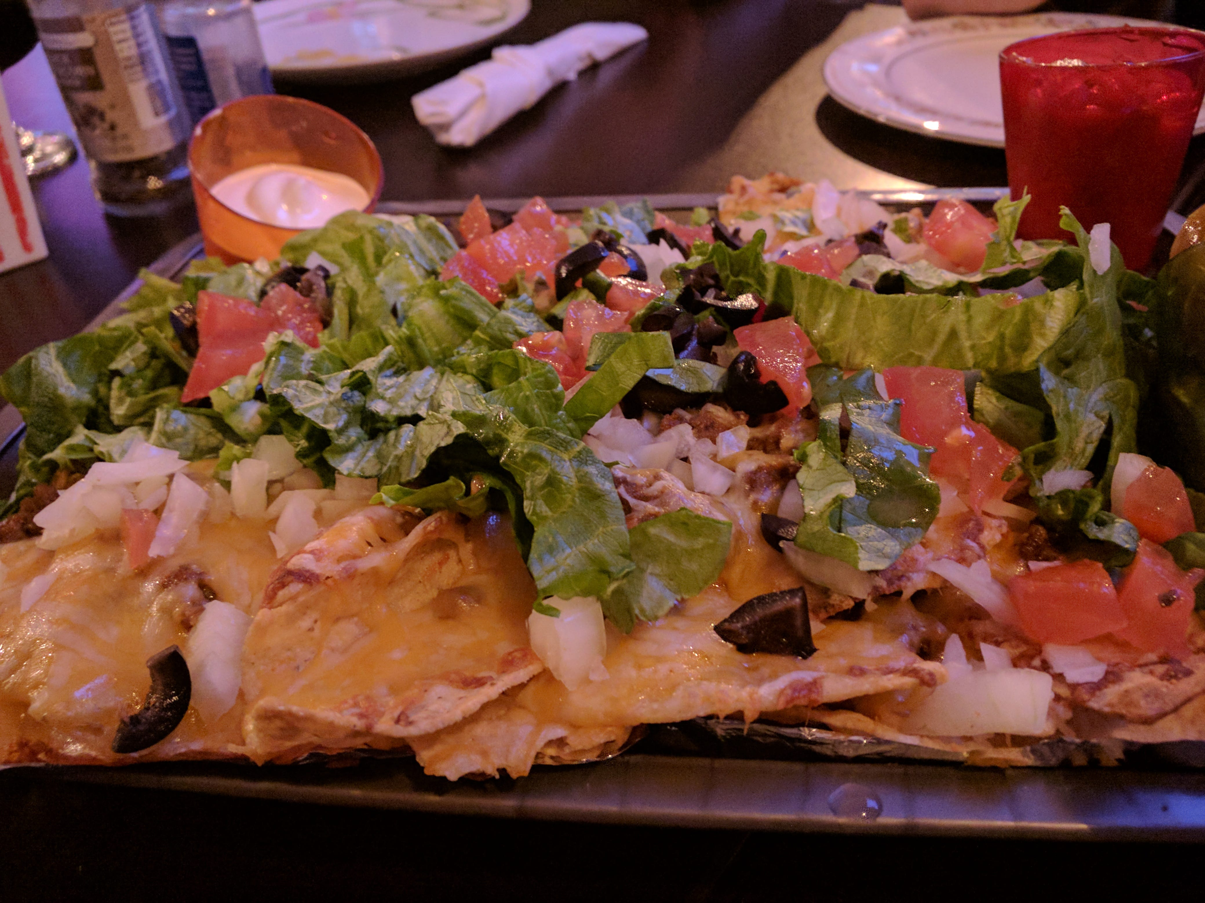 Cheesy, beefy nachos are covered with lettuce, black olives, tomato, and onions with jalapenos, sour cream and salsa at The Village Tavern.