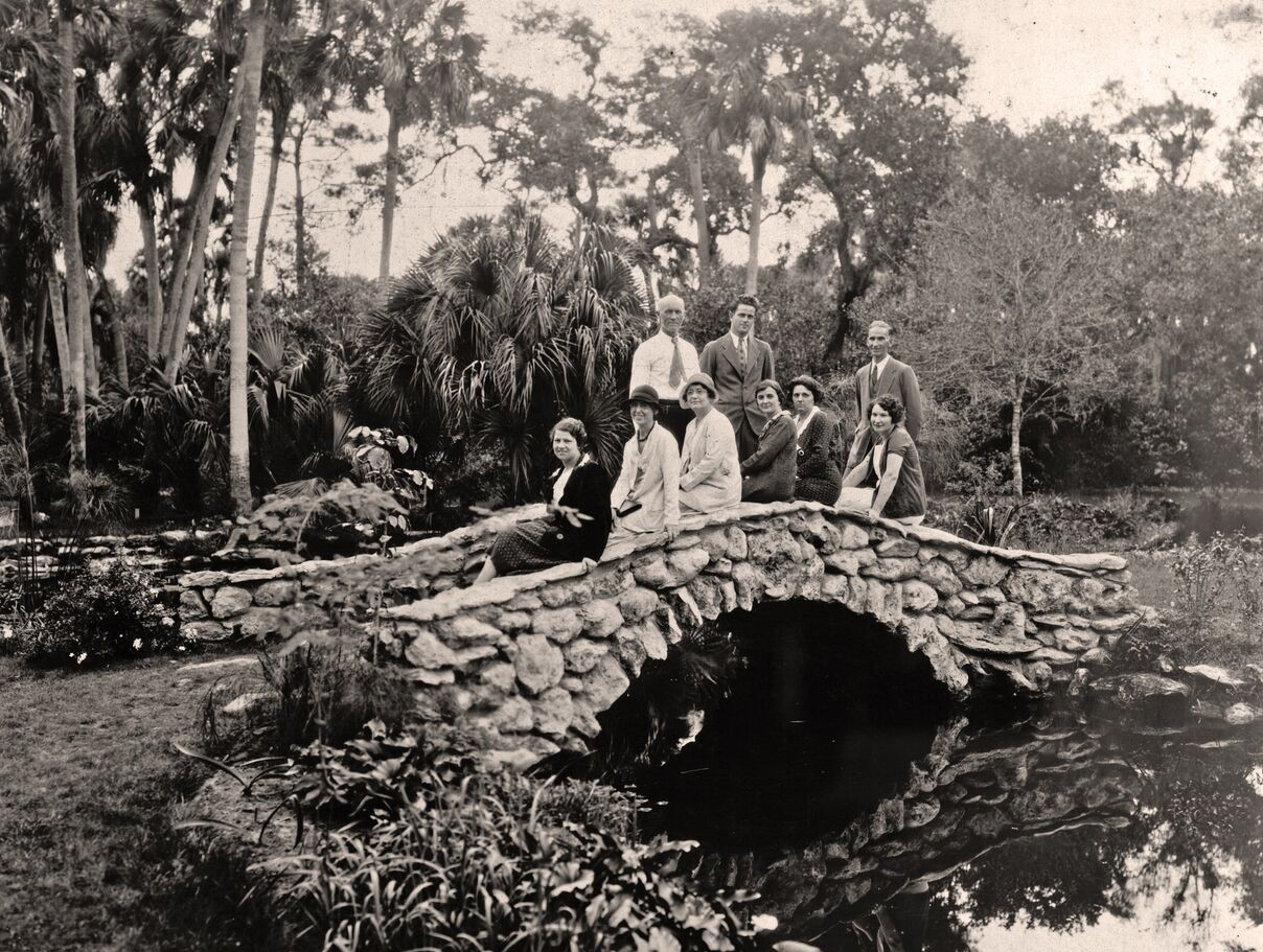 A group of people have their picture taken on McKee Jungle Gardens' stone bridge in 1935.