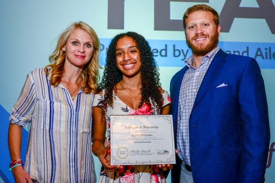 2019 Youth of Year Kayla Williams, center, accepts a $1,500 scholarship from Julia and Philip Busch and Southern Eagle Distributing.
