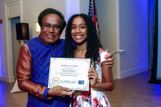 Dr. Shamsher Singh presents Boys & Girls Clubs of St. Lucie County 2019 Youth of the Year winner Kayla Williams with a certificate to participate as a chaperone for an upcoming Southeast Florida Honor Flight.