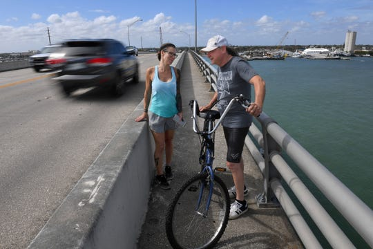"""Visiting from St. Louis, Missouri, Dennis Roemerman (left) stops to talk with  Gina Capparelli, a runner from Fort Pierce, as they stand alongside the traffic Feb. 9, 2019, atop the South Bridge in Fort Pierce overlooking the Indian River Lagoon, linking Fort Pierce to Hutchinson Island. """"It's a little scary on the bike, you feel like you are above your comfort level,"""" Roemerman said about the walkway on the side of the bridge."""