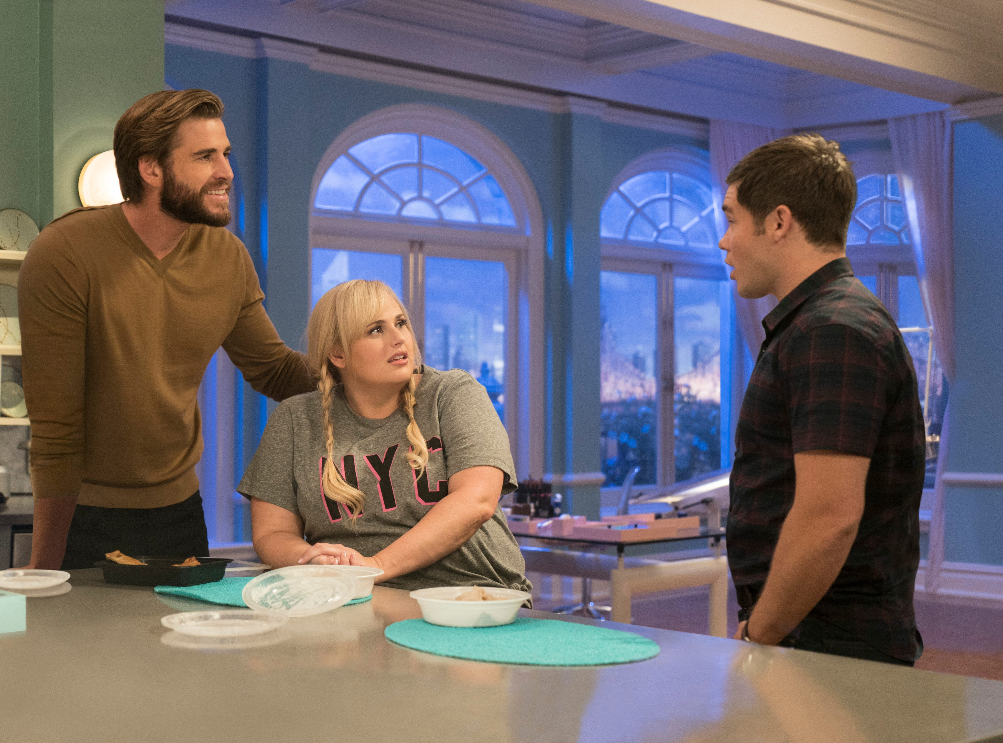 """This image released by Warner Bros. Pictures shows Liam Hemsworth, from left, Rebel Wilson and Adam Devine in a scene from """"Isn't It Romantic."""""""