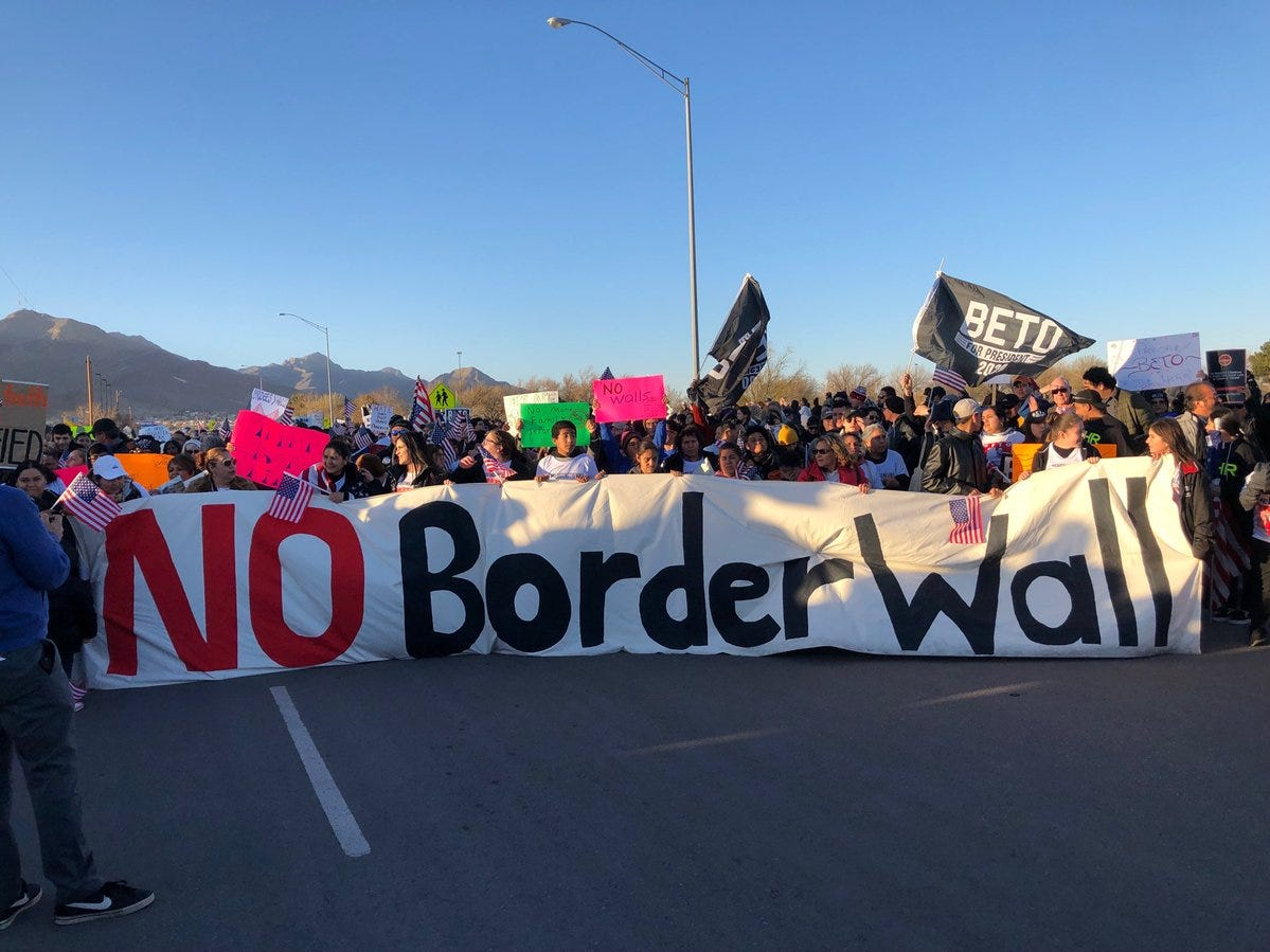 People at the counter-rally hold a banner against the border wall Monday.