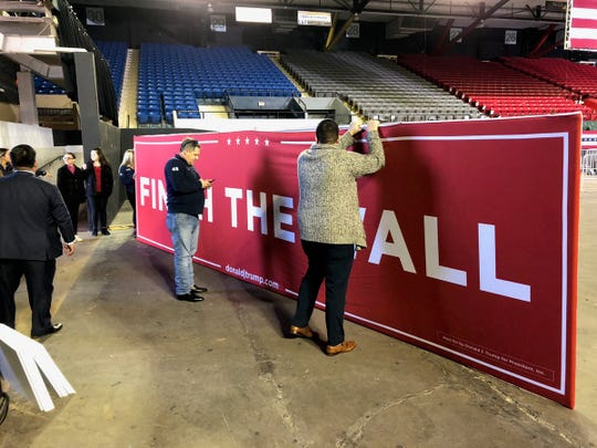 """Finish the Wall"" sign is brought into the El Paso County Coliseum ahead of President Donald Trump's visit, Feb. 11, 2019."