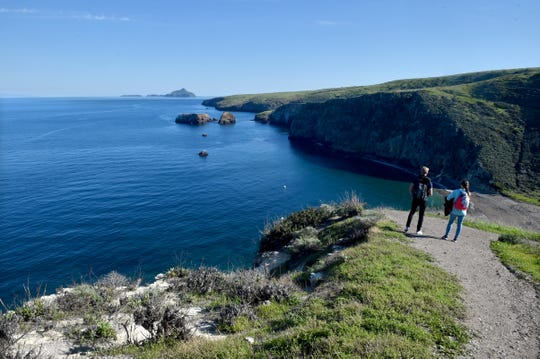 Visitors hike along a trail near Scorpion Anchorage on the east end of Santa Cruz Island in Channel Islands National Park.
