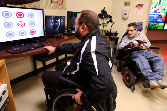 Peter Gagliardo, the adaptive sports coordinator at Helen Hayes Hospital, demonstrates an eye gaze game that people with no mobility can play, as volunteer Marc Simons looks on in their adaptive gaming room Feb. 11, 2019 in Stony Point.