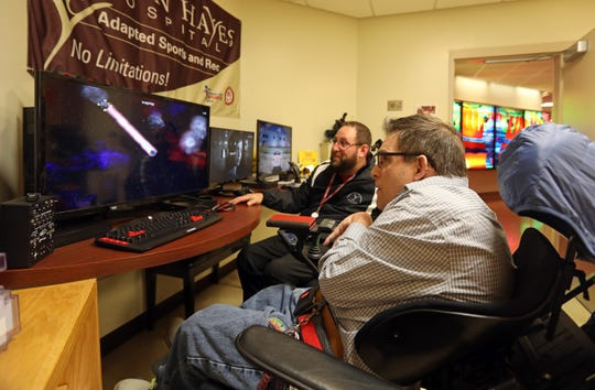 Volunteer Marc Simons, right, uses his eyes to play eye Asteroids as adaptive sports coordinator Peter Gagliardo looks on in the adaptive gaming room at Helen Hayes Hospital Feb. 11, 2019 in Stony Point.